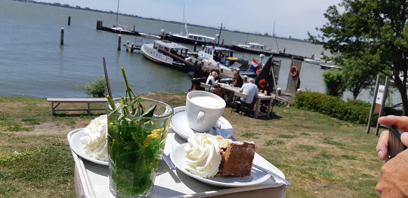 eerste bezoekers weer op forteiland pampus - met koffie, thee en taart op het zonnige terras, in de achtergrond zie je de haven en andere passanten zitten