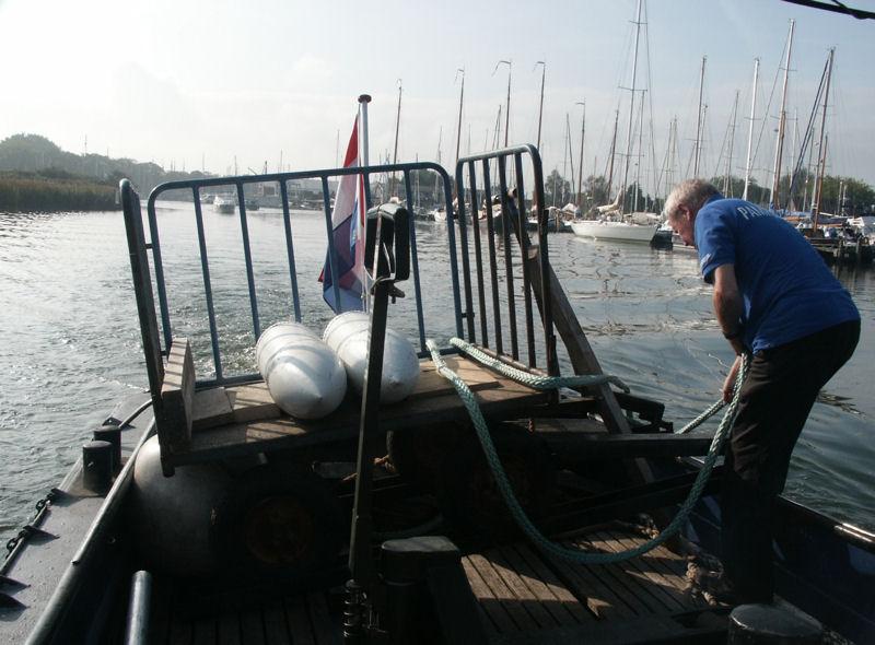 foto genomen vanaf de Vlet, een van de vrachtboten van Forteiland Pampus, met daarop twee witte grote pantsergranaten die bestemd zijn voor het forteiland, op de achtergrond de haven van Muiden en er staat ook een vrijwilliger van Pampus op de foto