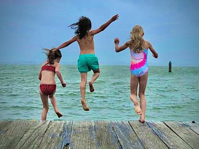 kinderen springen vanaf de zwemsteiger van pampus in het ijsselmeer