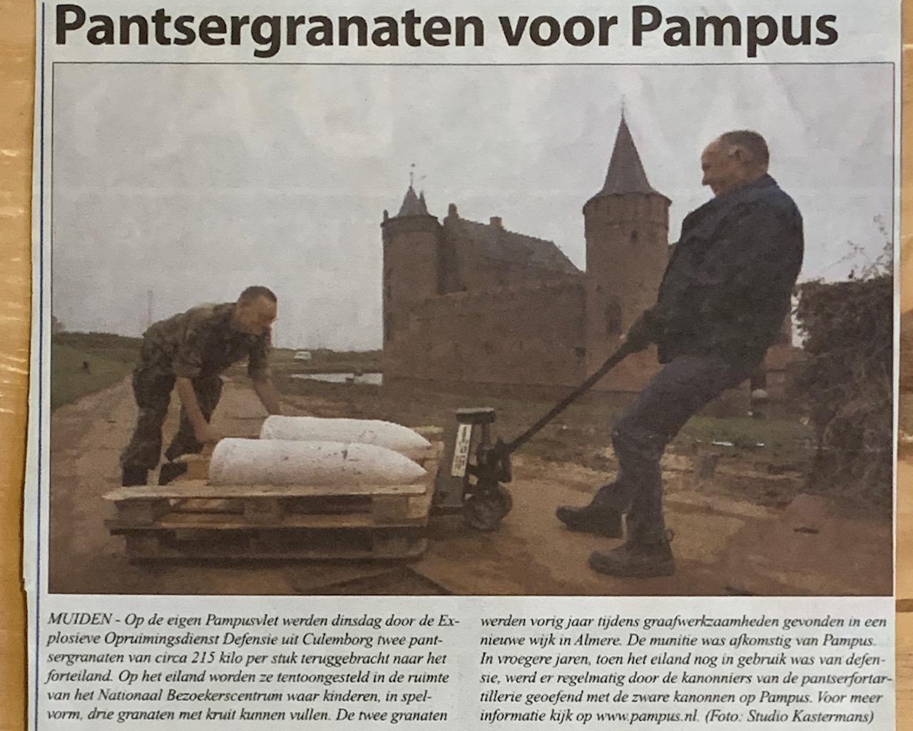 pantsergranaten voor Forteiland Pampus met twee mannen die een pallet sjouwen waarop twee grote, witte pantsergranaten liggen. Op de achtergrond zie je het Muiderslot liggen.