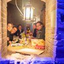 een doorkijkje in het fort op Forteiland Pampus met een gezellig lantaarntje en een groepje mensen die lekker aan het smikkelen zijn met een wijntje erbij, ze kijken lachend naar de camera en hebben het duidelijk naar hun zin tijdens dinerbeleving Winterlicht