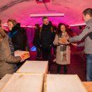 pop-up dinerbeleving Winterlicht op Forteiland Pampus met mensen die een kistje krijgen uitgereikt waarin allerlei lekkere hapjes verstopt zijn, de foto is genomen in het waterbassin, de grootste ruimte in Fort Pampus, de ruimte is met led-licht mooi roze uitgelicht