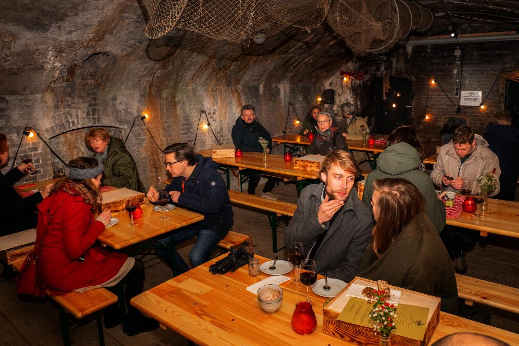 in het piratenhol zien we aan biertafels allemaal gasten zitten van Winterlicht, de dinerbeleving op Forteiland Pampus, de foto is genomen in het fort