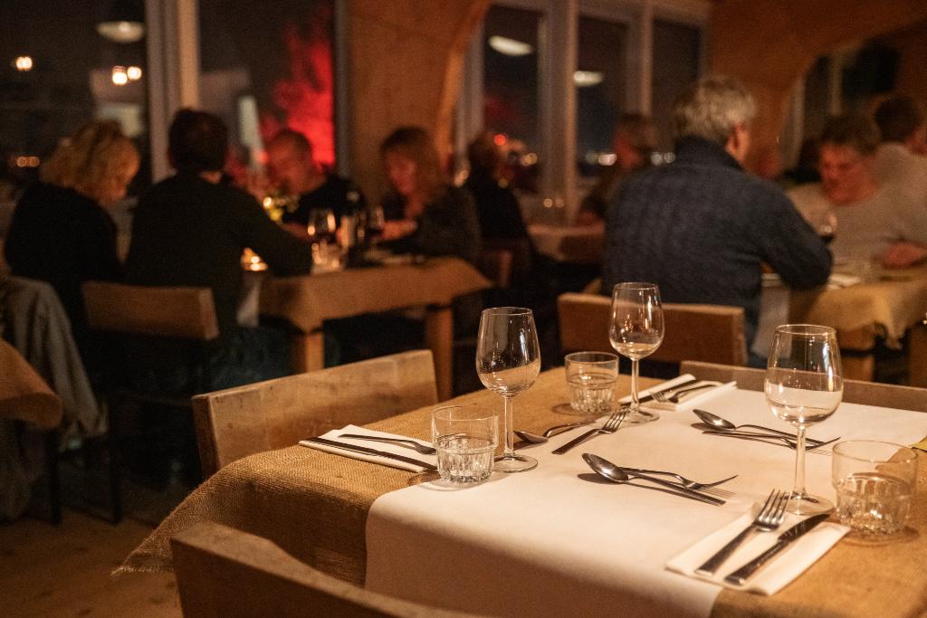 een leeg tafeltje maar mooi gedekt, op de achtergrond zien we mensen dineren in het restaurant Winterlicht op Forteiland Pampus