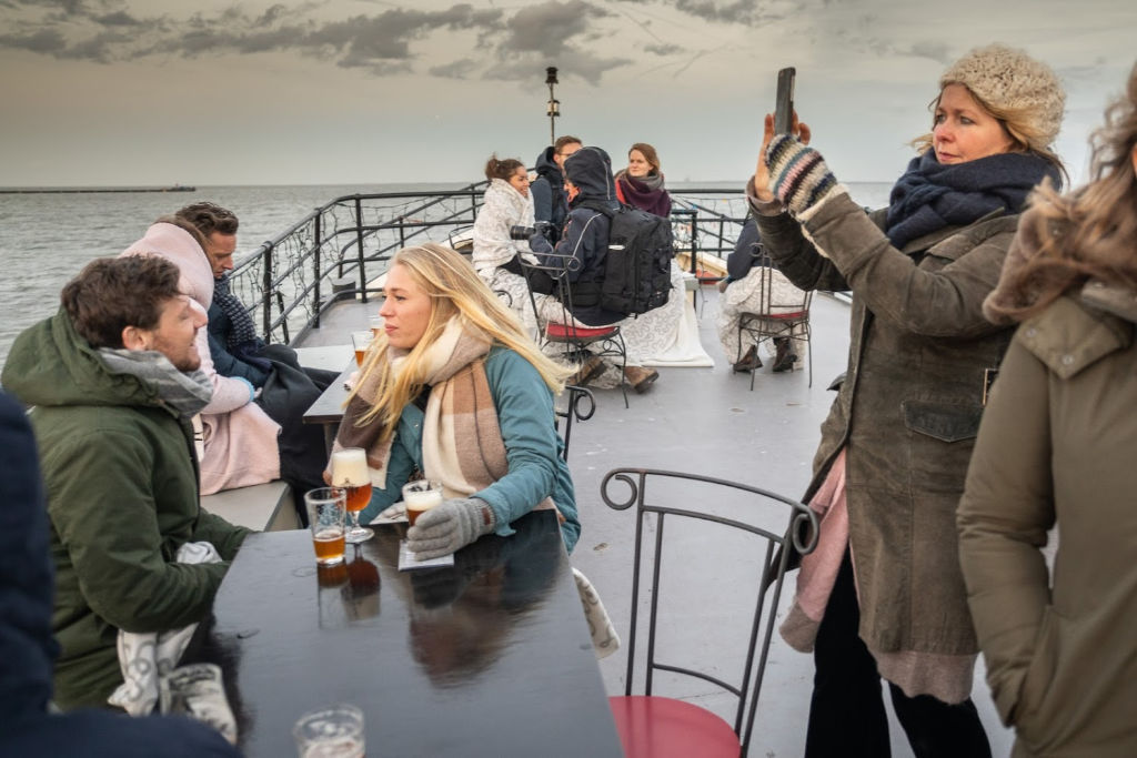 mensen met dikke mutsen, sjawls en winterjassen die genieten buiten aan boord van de klipper Sailboa die op weg is naar Forteiland Pampus, een vrouw maakt met haar mobieltje een foto, een stelletje zit aan tafel met een speciaal biertje in de hand, iedereen heeft het zichtbaar naar de zin en is op weg naar dinerbeleving Winterlicht
